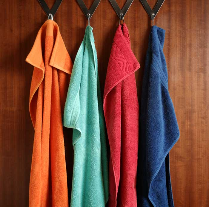 frottee towels of a family are hanging on iron hooks on a bathroom door.